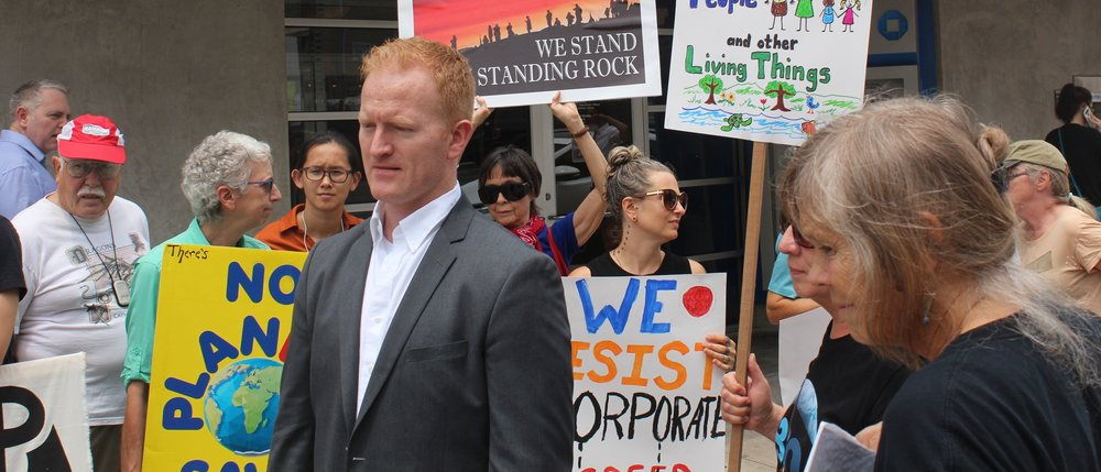 Derrick Crowe stands with local climate change activists to push financial institutions to divest from fossil fuels at a protest in Austin, Texas.