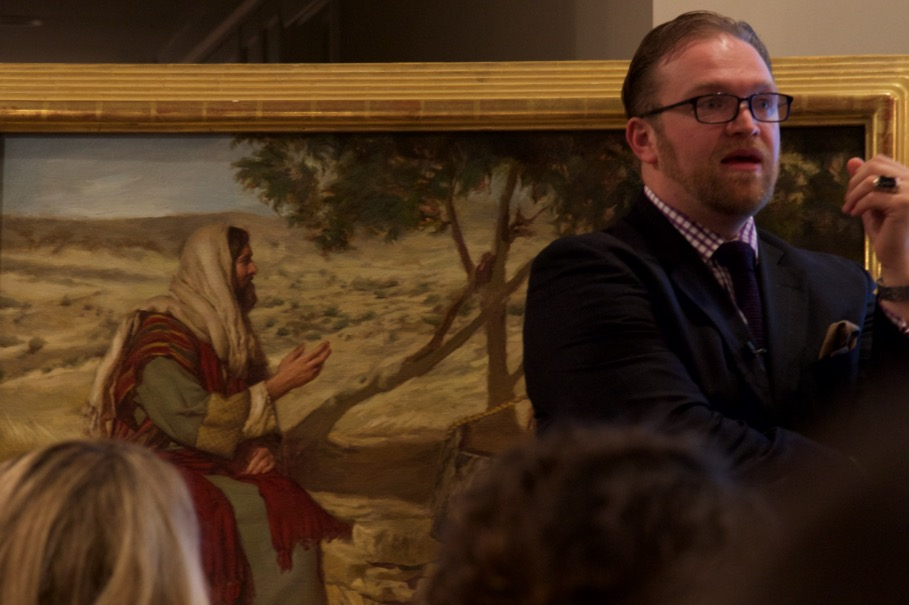 Dr. Micah Christensen leading a discussion on the role of LDS art enthusiasts and patrons, standing in front of a painting by Mary Sauer.