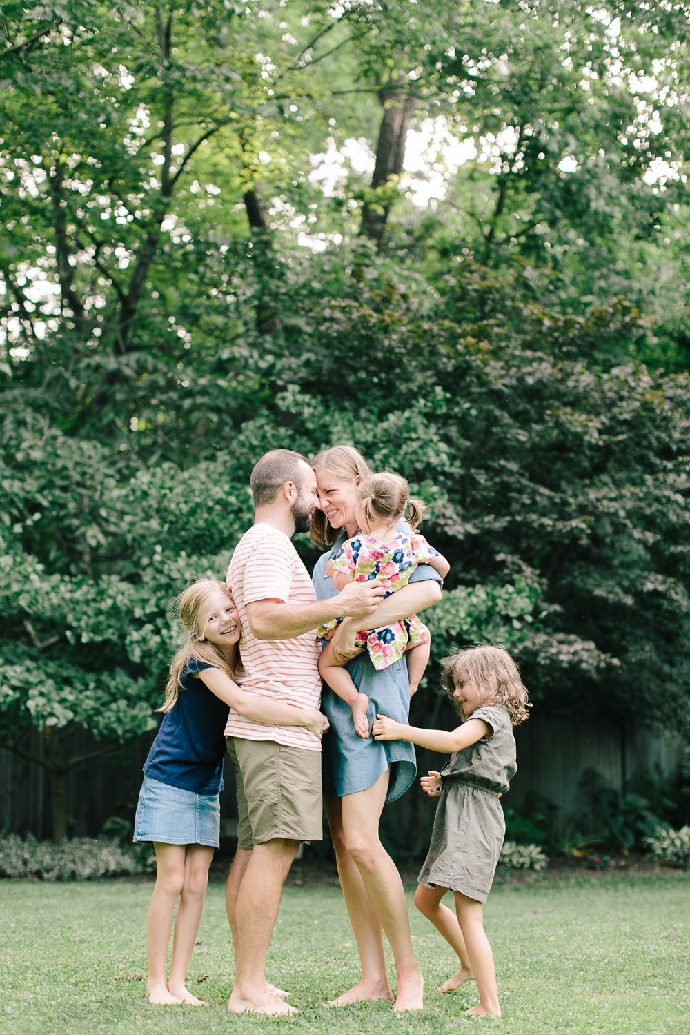 happy family hugging in back yard in home family photography
