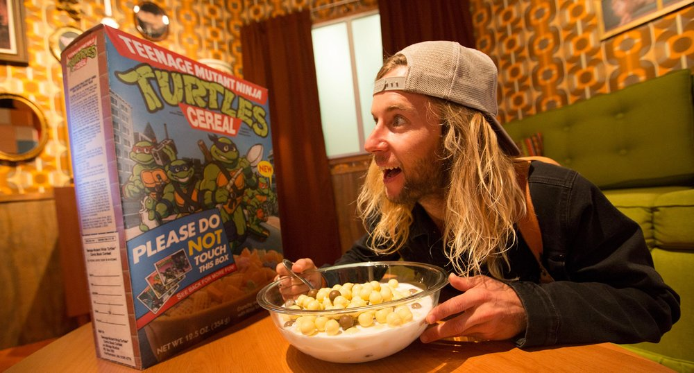 Person Eating Oversized Cereal in Exhibit Living Room