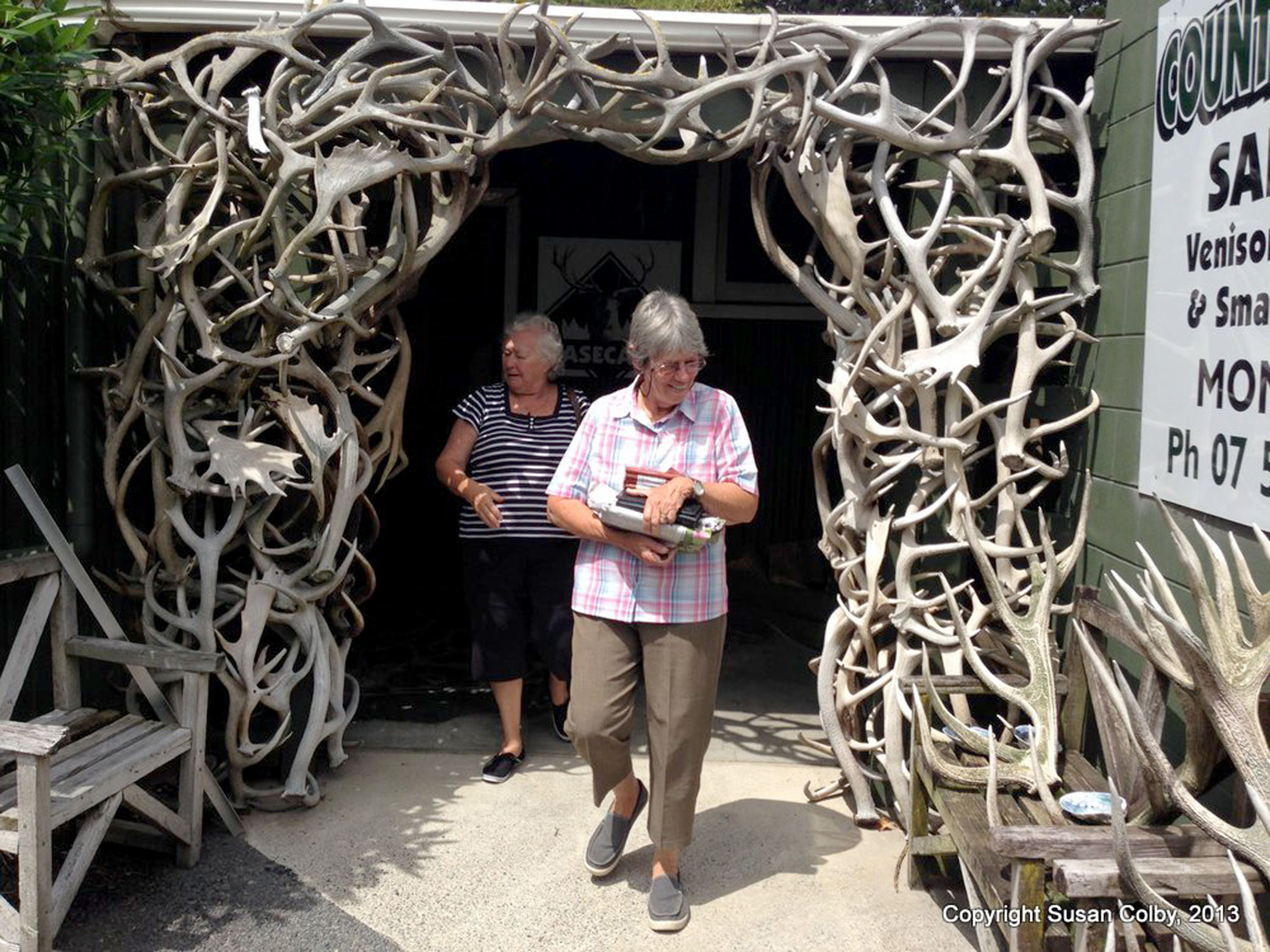 Zoze and Evelyn coming out through the antler arch doorway of Basecamp