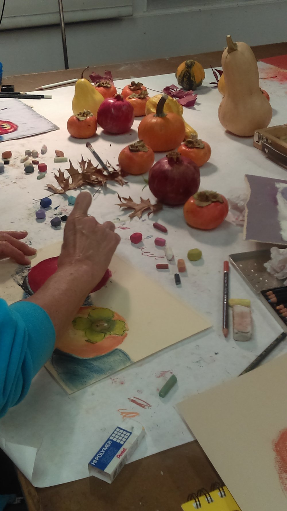 Student working with soft pastels and fall still-life