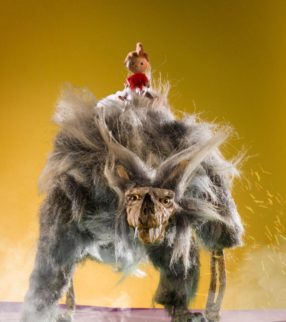El niño montando un lobo gigante.