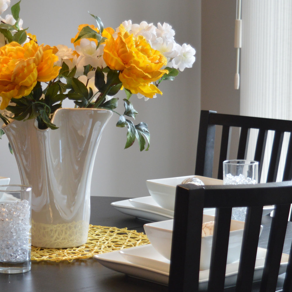 photo of dinner table set with plates, glasses and flowers