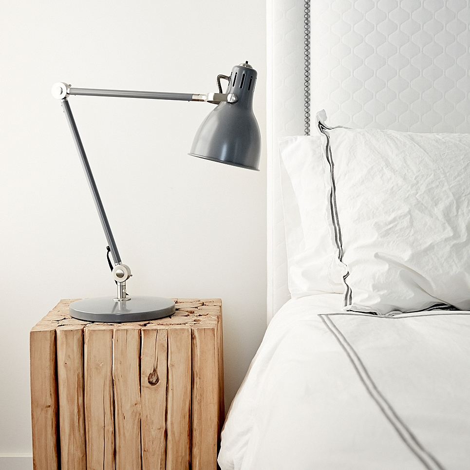 High-tech lamp on nightstand next to made bed