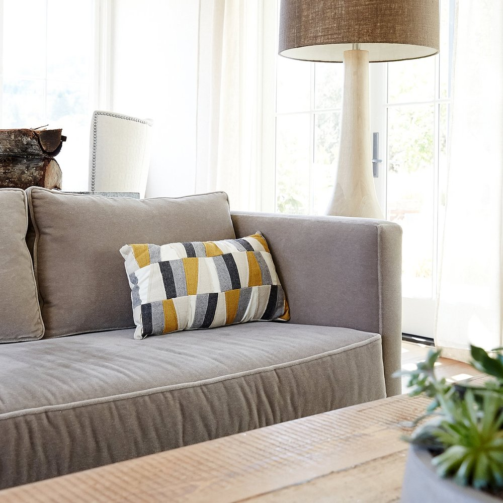 Couch, floor lamp and coffee table in living room filled with bright, natural light
