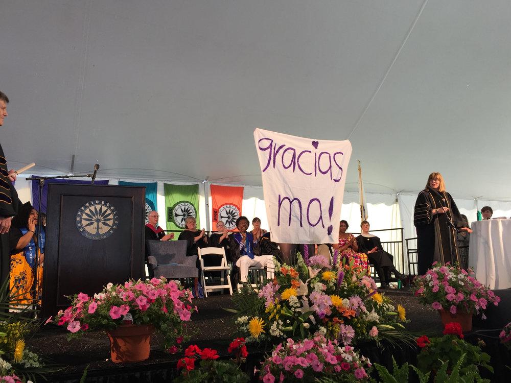 La autora en su graduación de universidad compartiendo un letrero para agradecer a su madre que está en el público. Hampshire College, mayo del 2016. Foto: Erin Corbett