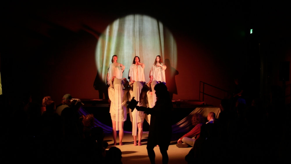 A Journey That Wasn't: Empire Folds - Broad Museum 6/30/18. Jiha Lee, Argenta Walther, Arlene Deradoorian, Tany Ling, Jess Basta, Stephanie Aston. Annie Gimas (not pictured: Salima Allen, Paloma Luna Maisonet, Community Chorus). Video still by Joanne Kim. Costume: 323 (and backwards dress by Nancy Stella Soto)