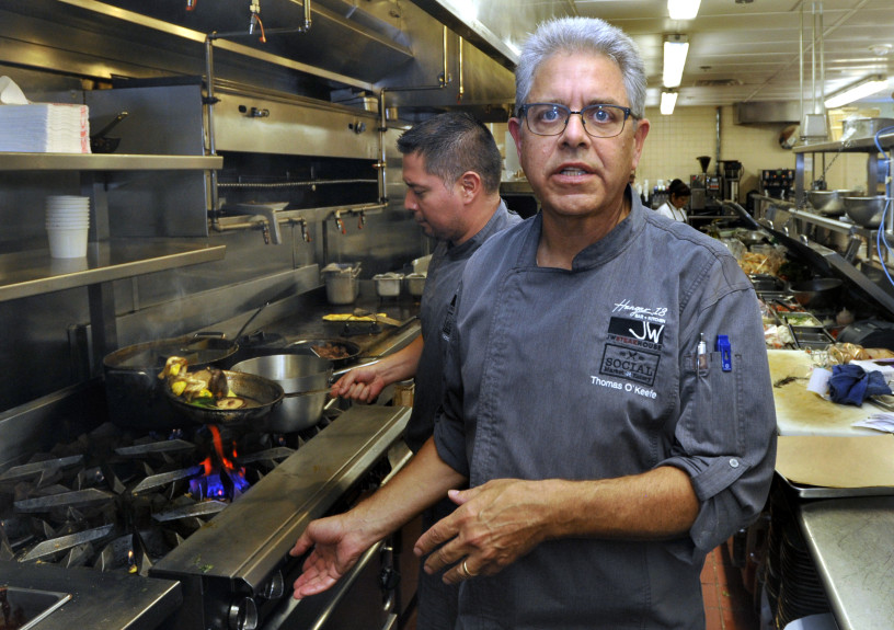 Executive Chef Thomas O'Keefe speaks while Executive Sous Chef Victor Miguel cooks in the background in the kitchen of Social Market and Eatery at the Los Angeles Airport Marriott Hotel, Thursday August 2, 2018. (Mike Mullen, Contributing Photographer)