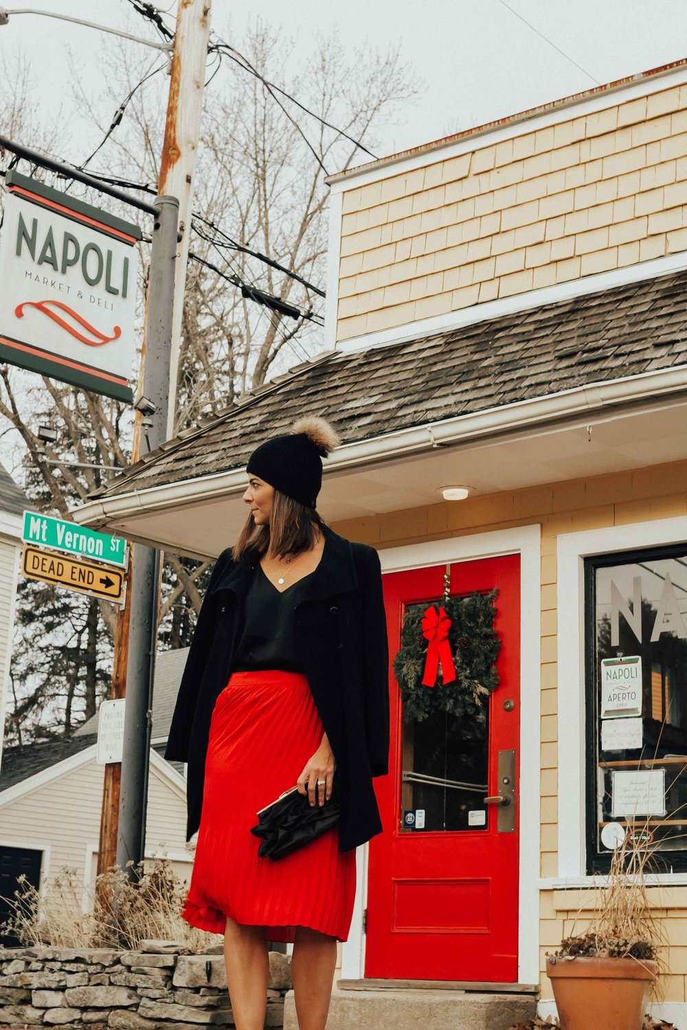 Shop the Look: - RED PLEATED SKIRT (UNDER $30)BLACK CAMIPEACOATPOMPOM HAT (similar)BLOCK HEELSINITIAL NECKLACE
