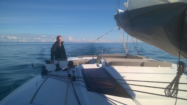 Under sail with light winds crossing the Strait of Juan de Fuca, Tom at the helm
