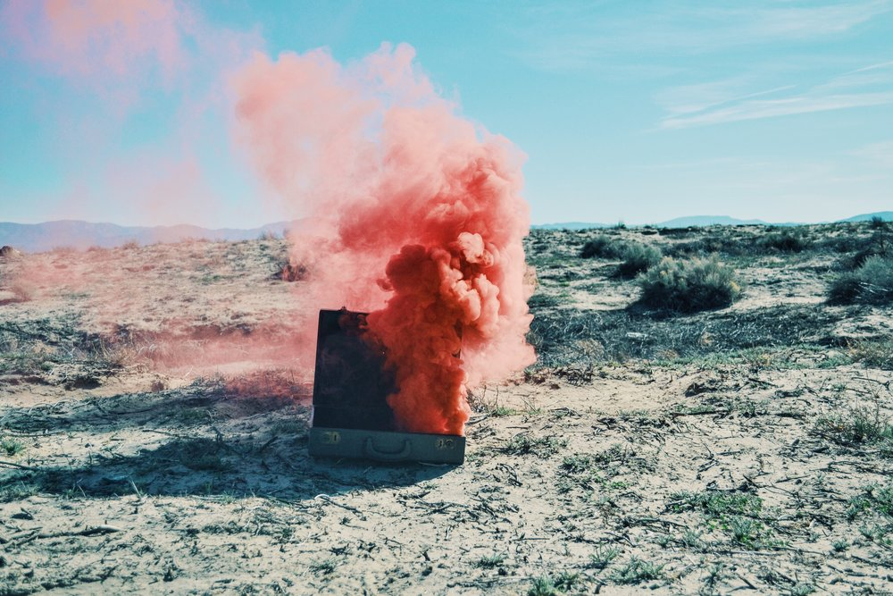 Suitcase with pink smoke