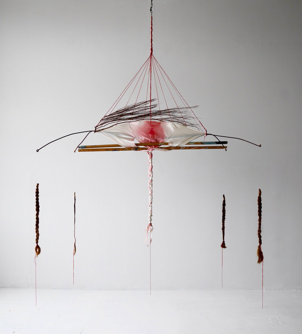"Rubedo or Reddening  72"" x 66"" x 36""  Wedding slip, cinnamon branches, broom sticks, braids of my mother's hair, braid of my hair, red thread, red dye, electrical wire, found metal  (2016)"