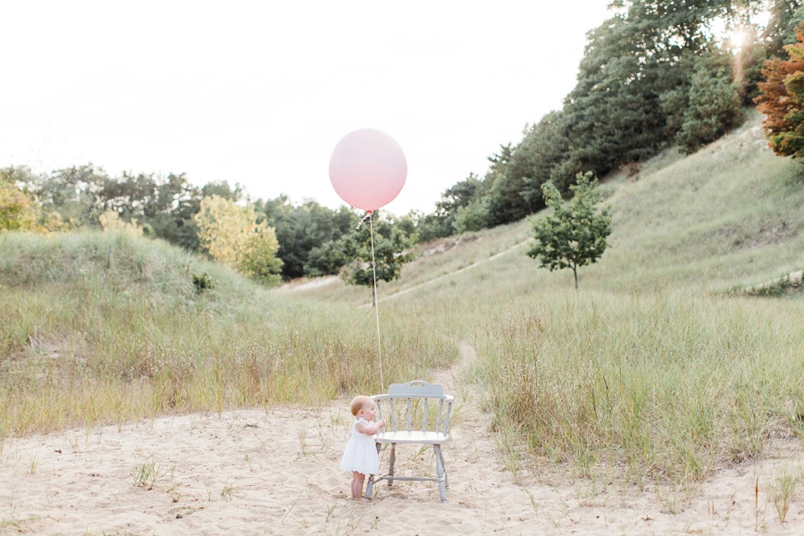 Pink ballon baby photography session in Grand Haven Michigan on a beach