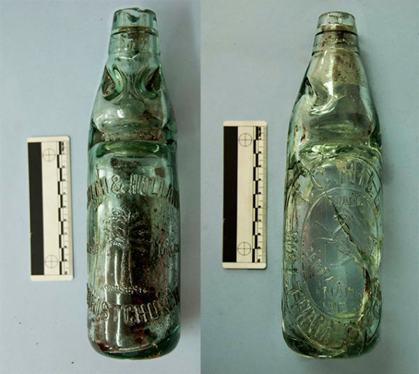 Two different variations on the Codd patent, both found in Christchurch. Note the wide indent on both bottles, there to keep the marble at the top of the bottle after it was opened. The smaller indents above it stopped the marble from resealing the bottle when the drinker tilted it a certain way. The bottle on the left is embossed with T. C. Hill, Waltham, ChCh, Zebra Trade Mark Regd (1904-1914), while the one on the right reads Smith & Holland, Christchurch, Trade Mark (c. 1920-1924). Image: J. Garland.