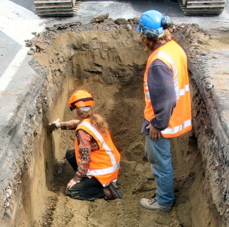 Jeanette McIsaac shows digger driver Duncan  stratigraphy in the side of the sewer excavation. Image: M. Trotter.