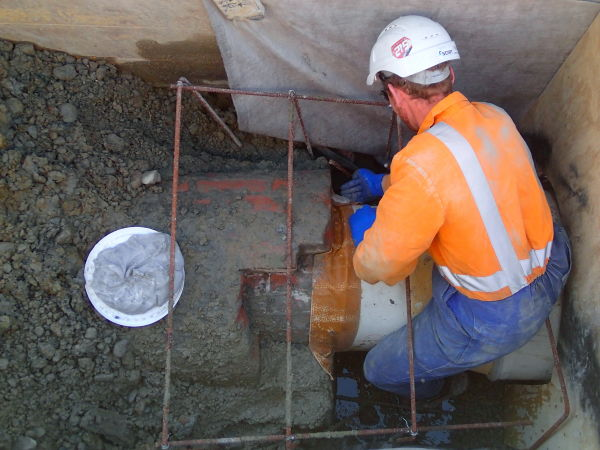Ben McConochie fits the upstream transition piece in place with epoxy mortar before the concrete is poured. Image: Hamish Williams.
