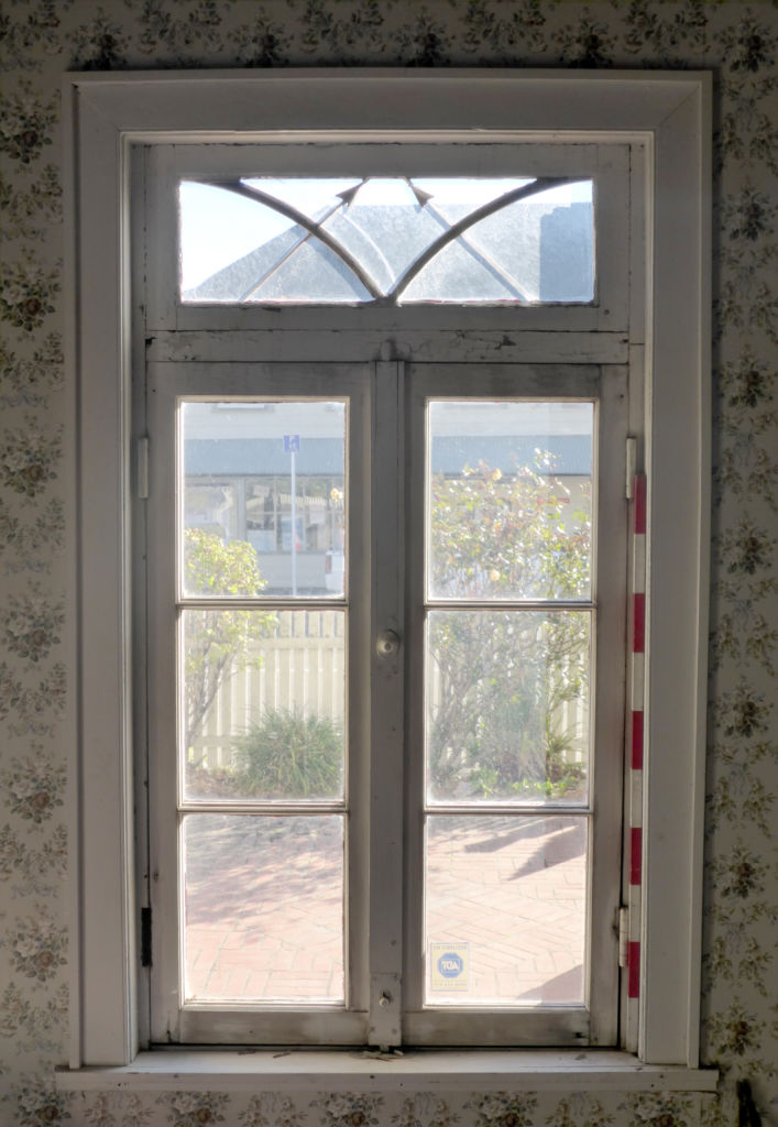 The window from the interior, set off by floral wallpaper and a shining autumn day. Image: L. Tremlett.