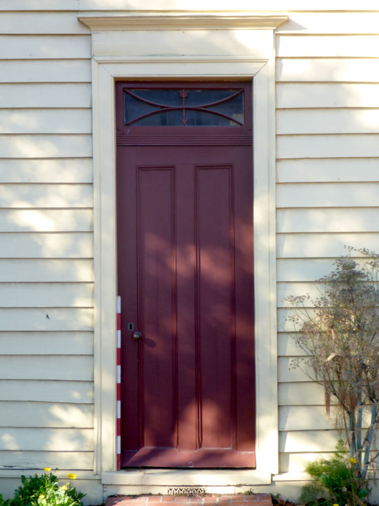 The front door to the cottage. Note the ventilation grate partly hidden behind the front step and the arrow decoration in the transom above the door. Image: L. Tremlett.
