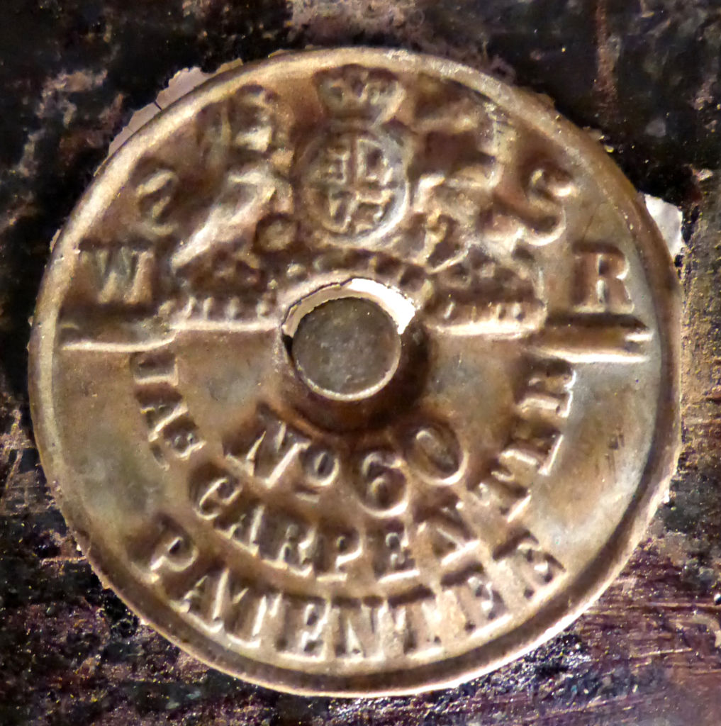"The maker's mark on the front door lock. It reads ""No. 60, Jas. Carpenter, Patentee"" on the lower half with the British crest on the upper half. James Carpenter was a well-known locksmith based in Willenhall, England, from the late 18th century until his death in 1844 (his business continued after his death under the name of Carpenter and Tildesley). The No. 60 was a famous patent of Carpenter's, patented in 1830 and popular around the world, including in the United States. Such locks are often found on buildings constructed in the 1830s and 1840s (Garvin 2001: 84), so that fits! Image: L. Tremlett."