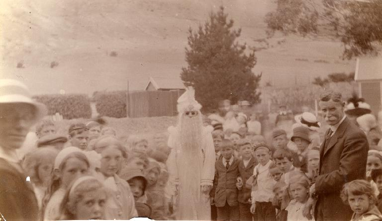 A ghostly looking Father Christmas (Mr. McMillan) at Heathcote School - Mrs. Yeale in foreground - Mr James Weir - Chairman School Committee - 1900 – 1910. Image: Christchurch City Libraries, File Reference: Gimblett 0009.