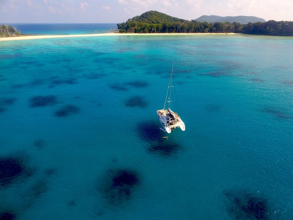 Andaman-Islands_drone-photo-of-blue-waters-lush-island-and-charter-yacht.jpg