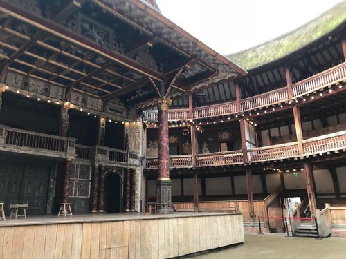 The inside of the Globe Theatre. The wooden columns on stage are painted to look like marble. The theatre has an open roof. Not great if it rains, but more authentic.