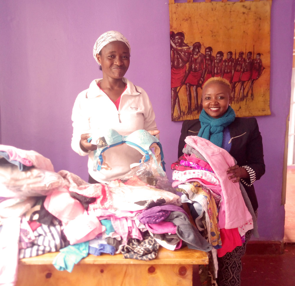 Esther (left) sorts her new clothing inventory with TOLI staffer Lucy (right).