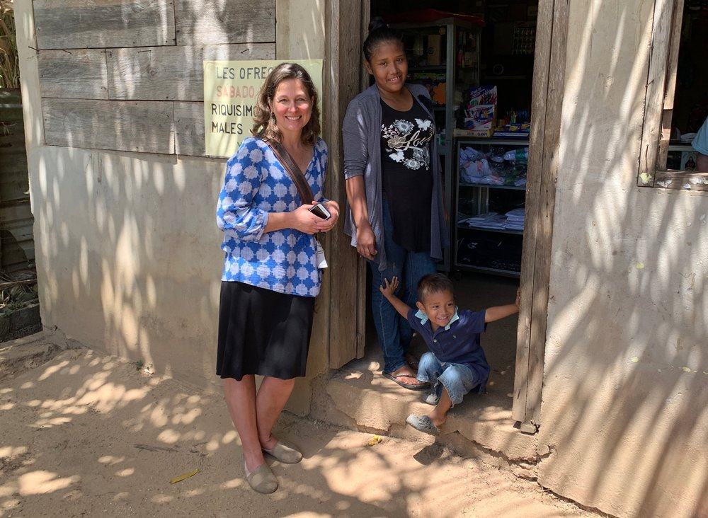 GENERATIONS:    Above, Shirley sits with her grandfather (center) and her father in front of their family store in Puerto Cabezas, Nicaragua. Below, Silhan and her son welcome Executive Director, Abigail McConnell, into her shop, built with the help of a TOLI microloan.