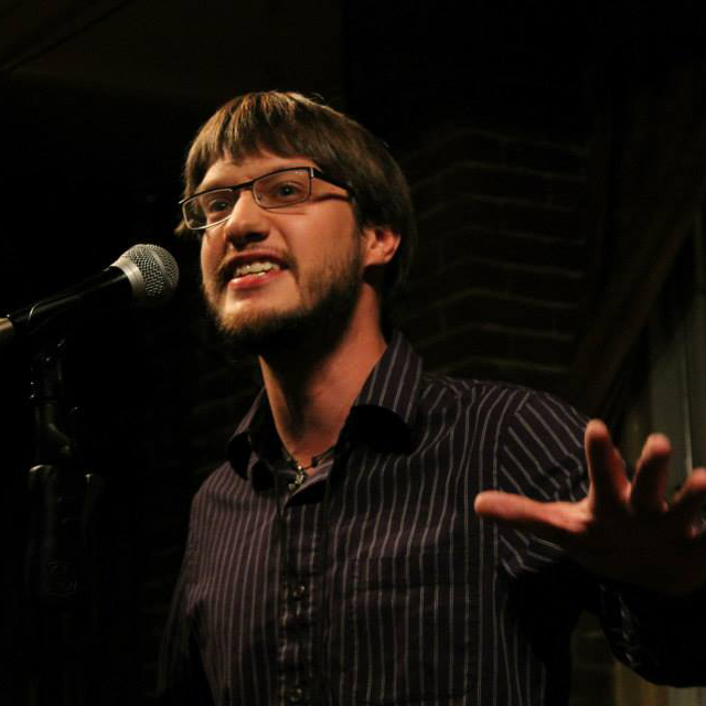 Nathan performing a poem with dramatic arm gestures.  Photo by Christopher Clauss