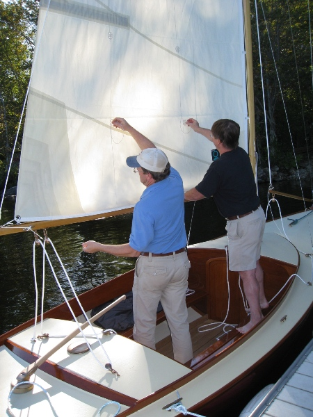 Bending on the sails. The sail is contained on the boom with a hand made Dutchman type system. 2mm Spectra lines are seized to the topping lift, woven through grommets in the sail, and terminated to bronze eye straps on the top of the boom.