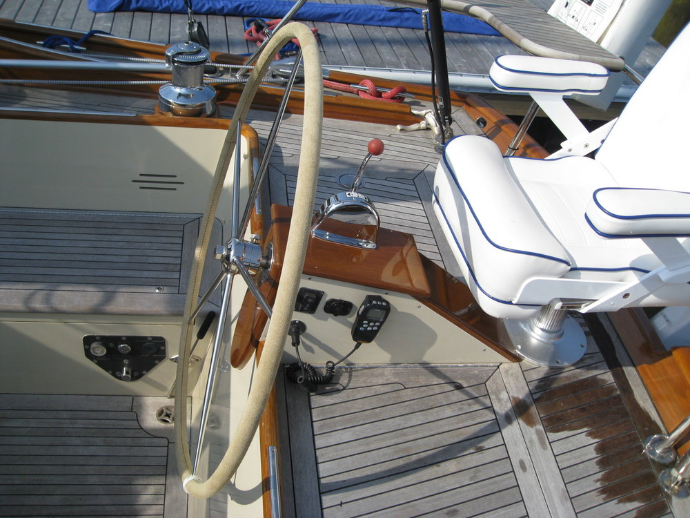 An elegant box hides the steering mechanism and provides a base for the throttle and VHF handset. The wheel hub can decouple the wheel from the shaft so it doesn't spin when the autopilot is steering the boat.