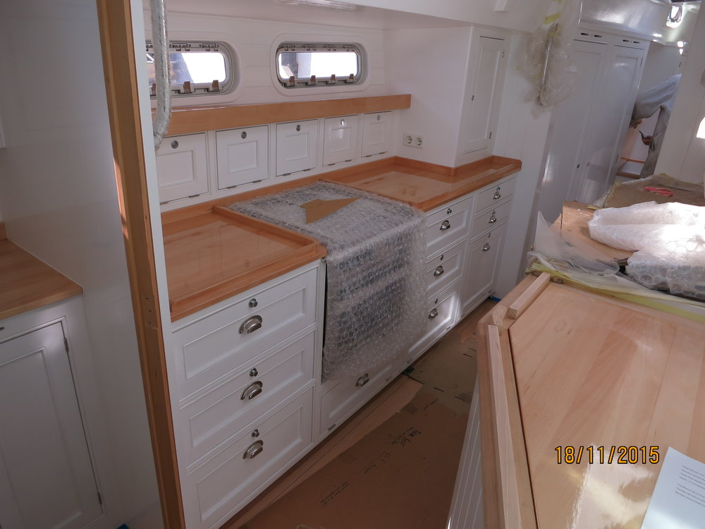 Looking forward into the galley. The bright interior motif is white paint with inset doors and lovely blonde countertops.