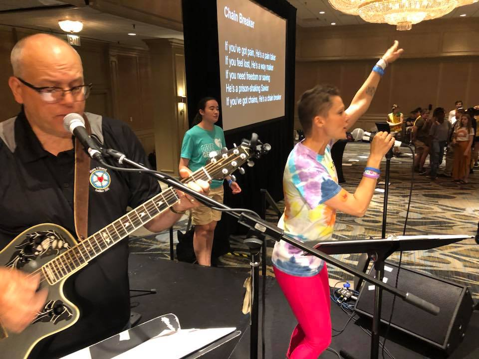 Pr. Mike Lembke on the left in the black shirt, playing guitar at this years Youth Gathering in Houston. His daughter, (on the right in Tie Dye T) Pastor Heidi Johnston leads singing.