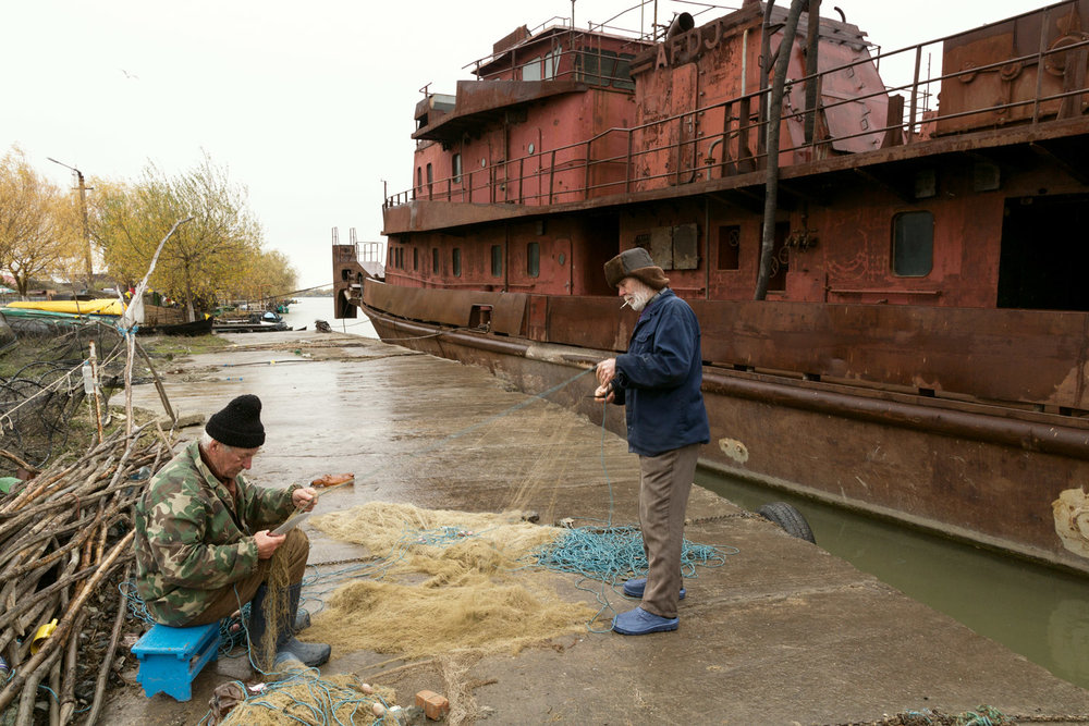 Sulina, Romania, November 2017. Two old sailors working on fishing nets.