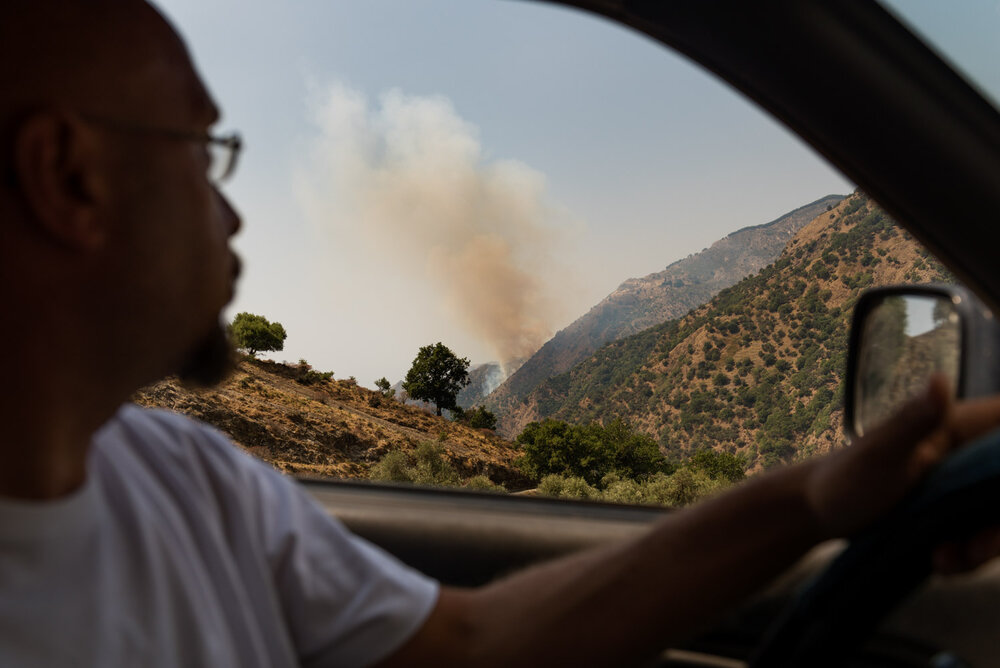 """Salvatore Natoli (42), a volunteer for a firefighter cooperative, spots a wildfire near the town of Roghudi Vecchio, on the Aspromonte National Park borders, August 2018.  Salvatore is the head of the San Luca Cooperative, which coordinates about twenty local volunteers: """"there was a project to demolish this land,"""" he says, speaking of the great amount of fires that damage Calabria every year."""