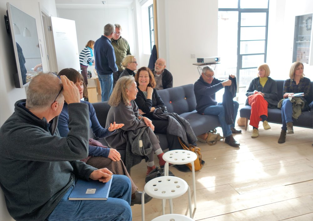 Events take place in the Living Room upper floor, siting on sofas and stools in an informal atmosphere. Here we have a friendly interval during a gallery discussion event.