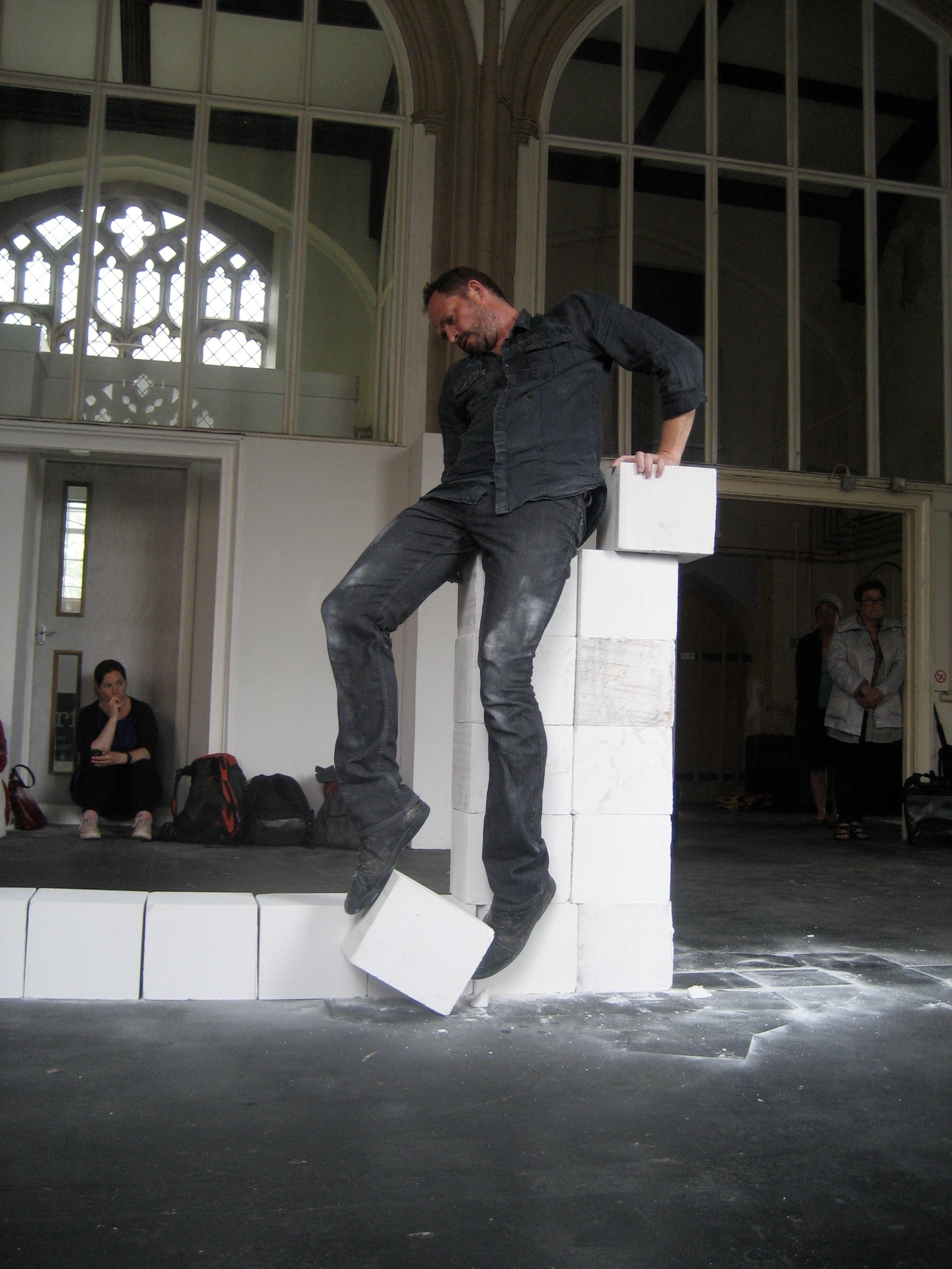 Claude Cattelain  For the performance 'Colonne empirique en ligne', he reconstructs a horizontal line of white Ytong blocks into a vertical column, moving them one by one from their ground line. In doing so, his body must not touch the ground, so the column becomes both his task and his perch. His balance is increasingly perilous, grasping the next block becomes ever more challenging and eventually impossible. Here it is being performed in Norwich in 2014 as part of a European cross-channel 'Interreg' funded programme 'Time and Place'. fabrica.org.uk
