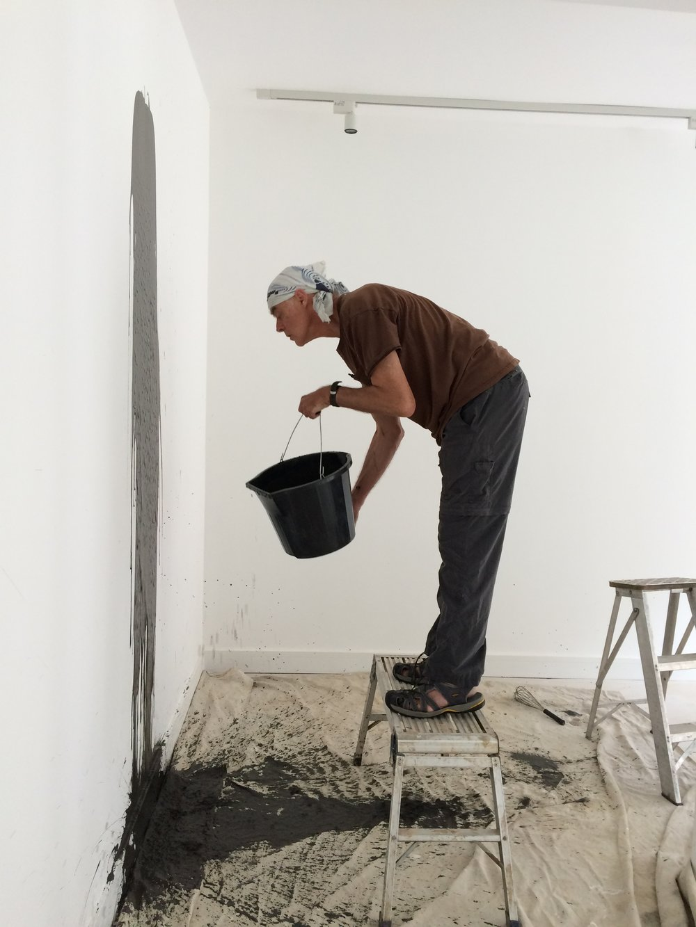 Richard Long inspecting the progress of the mud drawing