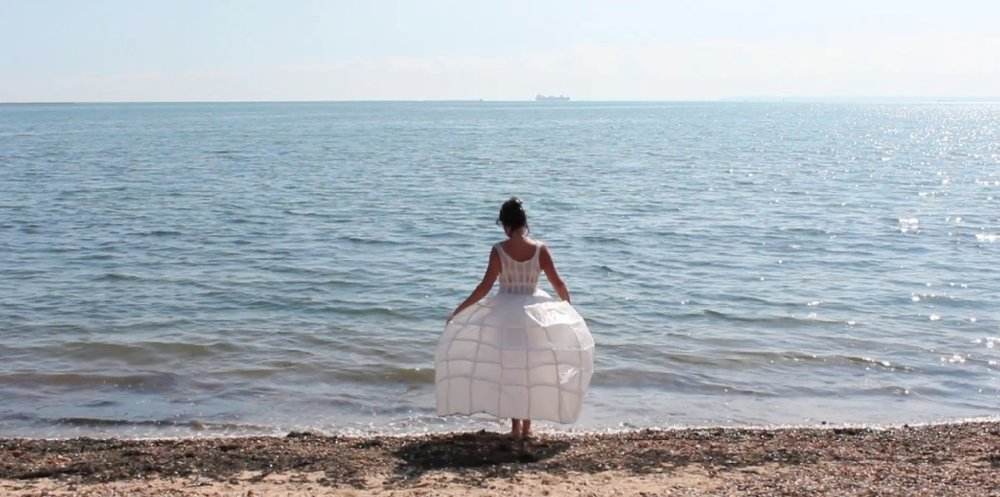Dress, sea; a video installation by Lynn Dennison. The artist performs this mysterious ritual, walking slowly into shallow waters of the sea, until she is submerged. The work makes an interesting parallel to Simon Faithfull's 'Going Nowhere 1.5' and in the gallery they are seen opposite each other.