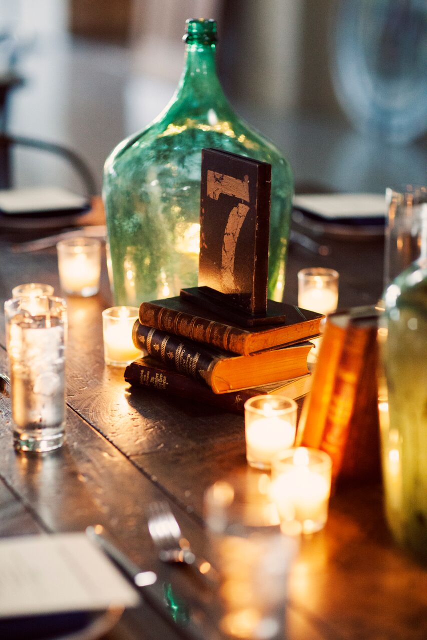 Old books and glass water jug decor   Planning By Wrap It Up Parties  Artifact Events