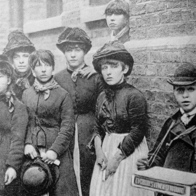 A group of matchwomen leaning against a wall