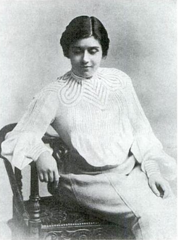 Olive Christian Malvery, seated and wearing a white blouse, face tilted down