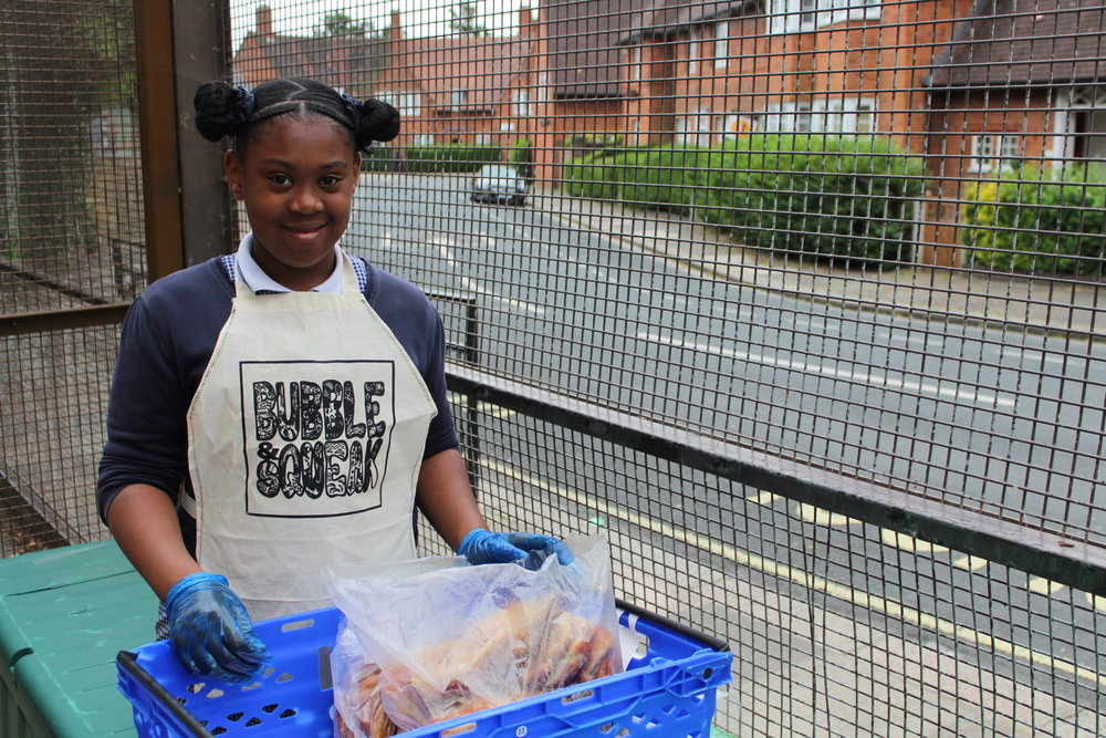 Bubble & Squeak volunteer distributing surplus bread (collected by local parent from a bakery)