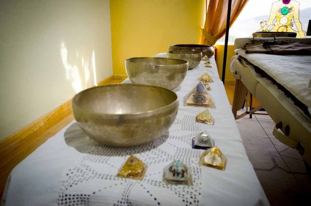 Singing bowls and healing crystals for vibrational therapy.