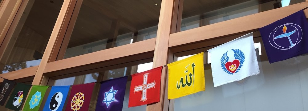 flags mark the sophia fahs commons in  the religious exploration area. the information and signup table is just outside this space.