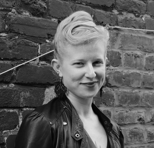 [image description: b&w photo of hannah harris-sutro, a white femme with dimples and pinned-up blonde hair in a leather jacket, smiling in front of a brick wall with a white cable running across it. photo by sj vriend.]