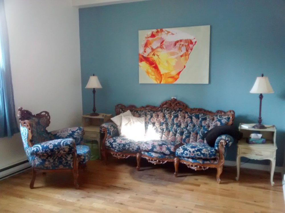 [image description: a bright office with a blue wall on which is hanging a painting of an orange & yellow citrine by sj vriend. in front of the blue wall is an antique, ornate sofa and armchair, upholstered in blue and pink floral, with two end tables and lamps. the sunlight from the window on the left edge of the photo makes a bright spot on the sofa.]