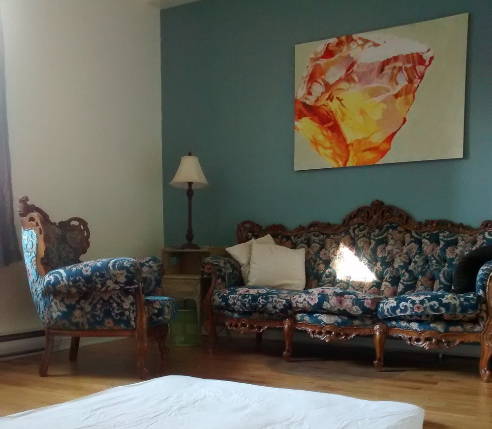 [image description: a picture of hannah's office, which has wooden floors, one white wall, and one blue wall. there is an antique carved wood armchair and sofa upholstered in blue velvet with a pink floral pattern, and a blanket, two pillows, and a patch of sunlight from the window on the sofa. between the sofa and the armchair there is a side table with a lamp, and on the floor you can see the bottom edge of a thin white shiatsu mat. on the wall over the sofa, there is a closeup painting of an amber gemstone in bright red, orange, and yellow.]