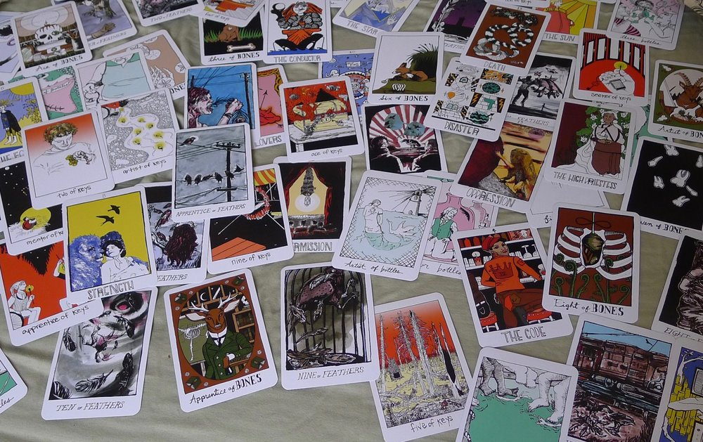 [image description: dozens of cards from the  collective tarot  spread messily over a pale green cloth. photo by hannah harris-sutro.]
